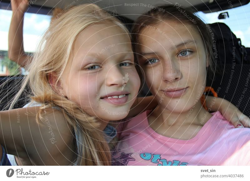 Smiling sisters on a car trip: blonde and brown-haired. Two girls of different ages are smiling, hugging each other, inside the car. teenage laugh emotion