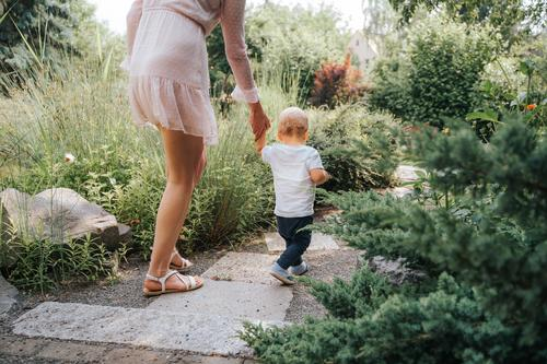 toddler learning to walk with the help of his mother outdoors adorable baby bonding boy child childhood crawl crawling cute emotions explore exploring