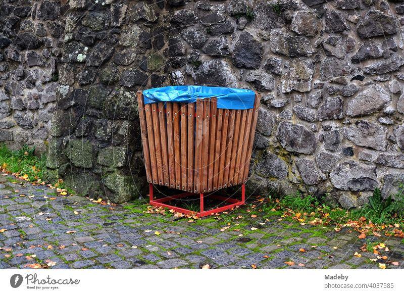 Rubbish bin made of brown wood with blue plastic bag in front of old brickwork in the courtyard of Gleiberg Castle in Wettenberg Krofdorf-Gleiberg near Giessen in Hesse, Germany