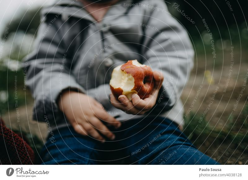 Close up child hand holding an apple Apple Child Eating Colour photo Exterior shot Nutrition Healthy Organic produce Day Apple tree Food Authentic Fruit