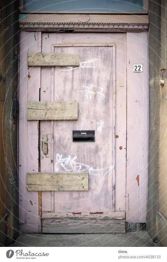 lockdown door lost places Broken board nailed Old building renovation case Wood 22 House number Mailbox Entrance locked tight graffiti Pink
