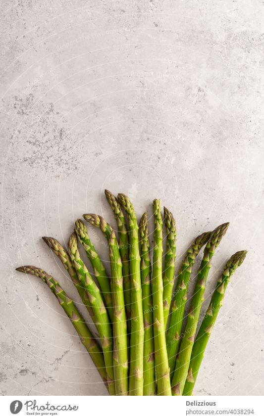 A bundle of fresh green asparagus on a grey background, copy space, vertical vegan flat lay cooking ingredients healthy vegetarian raw clean ready-to-eat