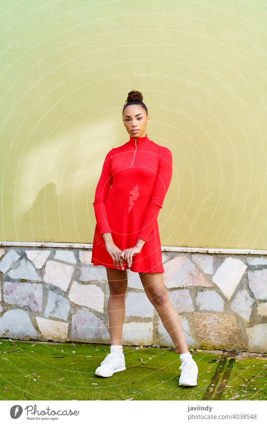 Young mixed woman in red dress with a serious expression in urban background. black bow hairstyle model beauty fashion pretty portrait girl young female person