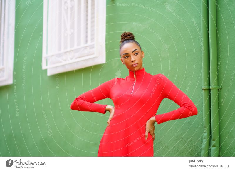 Young mixed woman in red dress in front of a green wall black bow serious hairstyle model beauty fashion pretty portrait girl young female person lady summer