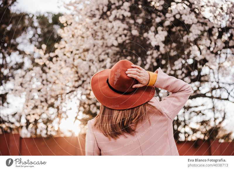 back view portrait of young woman wearing modern hat at sunset in park. beautiful almond tree flowers background. Springtime and blossom spring trees outdoors