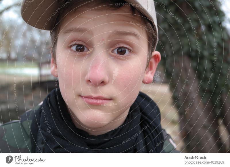 Lausbubgesicht mit Capy Junge Kind Gesicht Portrait Basketballmütze frech jung braune Augen Blick dunkelblond draußen Freizeit 8 - 13 years männlich