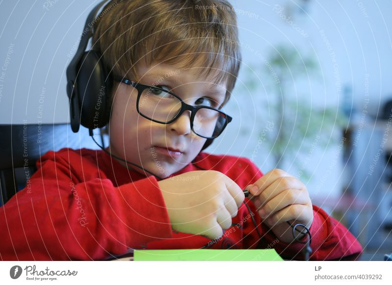 child wearing glasses and headphones  looking very serious away from the camera sceptical doubts uncertainty Infancy reality Experimental Background picture
