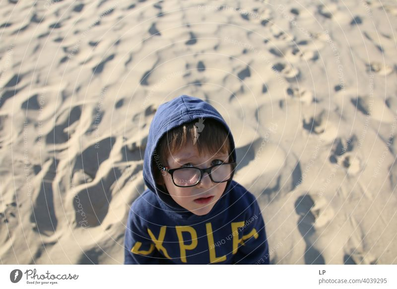 beautiful child wearing glasses and a hoodie  looking very serious into the the camera puzzled Perplexed sceptical scepticism doubts Doubt hestitate uncertainty