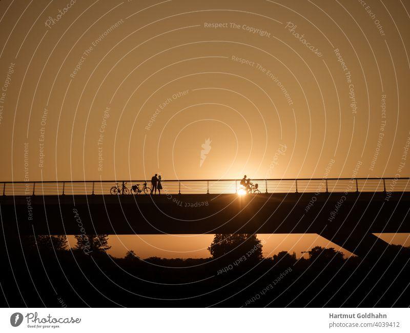 Silhouette von einen Paar das sich kurz vor Sonnenuntergang auf einer Brücke trifft. treffen Begegnung kontrast Rendezvous Personen Sonnenaufgang Fahrräder zwei