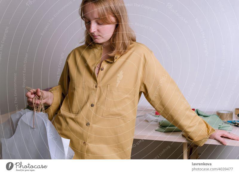 Female in yellow shirt holding paper dress patterns in her workshop tailor craft dressmaker fashion clothing occupation handmade designer textile atelier