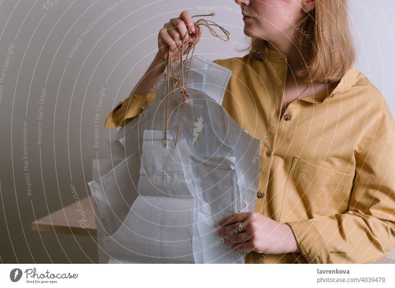 Female in yellow shirt holding paper dress patterns in her workshop tailor craft dressmaker fashion clothing occupation handmade designer faceless textile