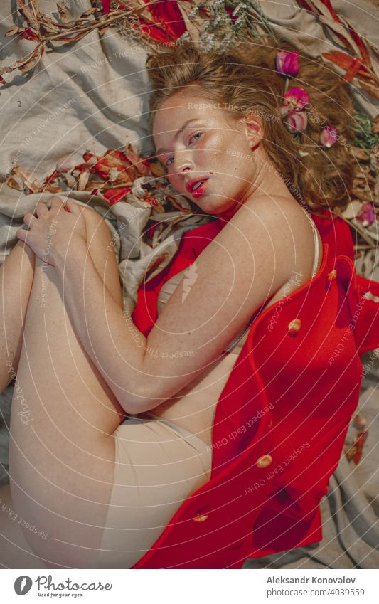 Young red haired woman in beige underwear lie on grey linen fabric under orange coat with flowers in her hair beauty Red Orange Hair Freckles Naked Young woman