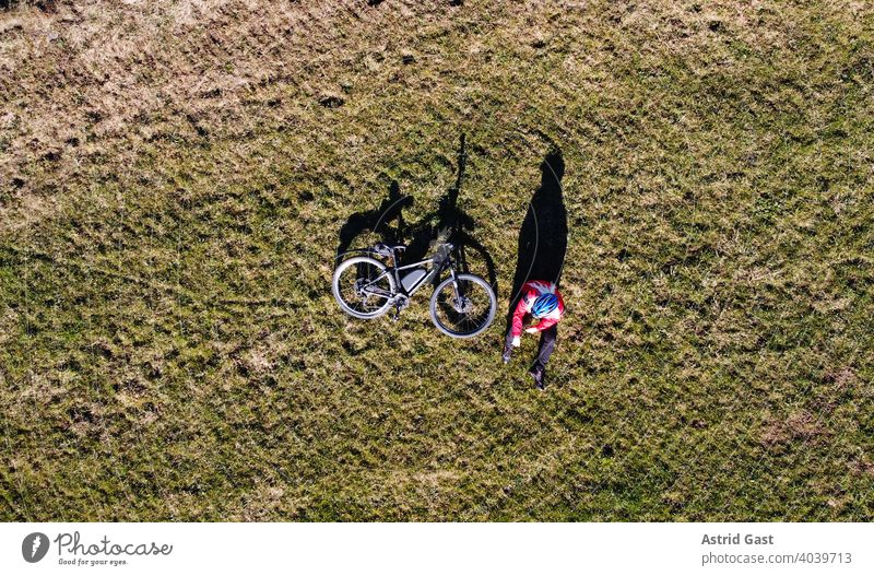 Aerial shot with a drone of a cyclist with bike on a meadow with light and shadow Aerial photograph drone photo Spring Sports Cycling Bicycle Woman
