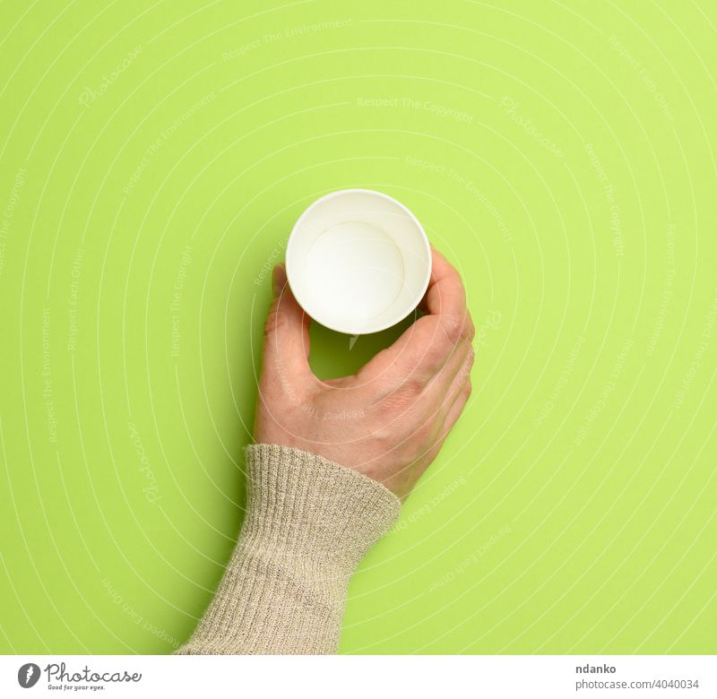female hand holding empty paper disposable cup on green background coffee container dishware drink caucasian arm beverage blank breakfast cappuccino cardboard