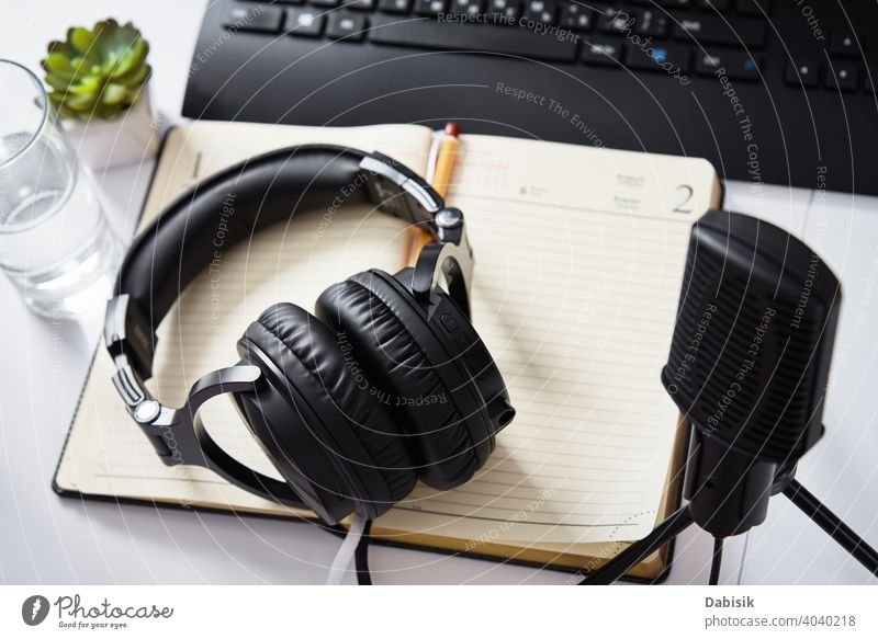 Microphone and headphones on the table, top view. Radio podcast workplace microphone audio radio online technology keyboard remote education learning e-learning