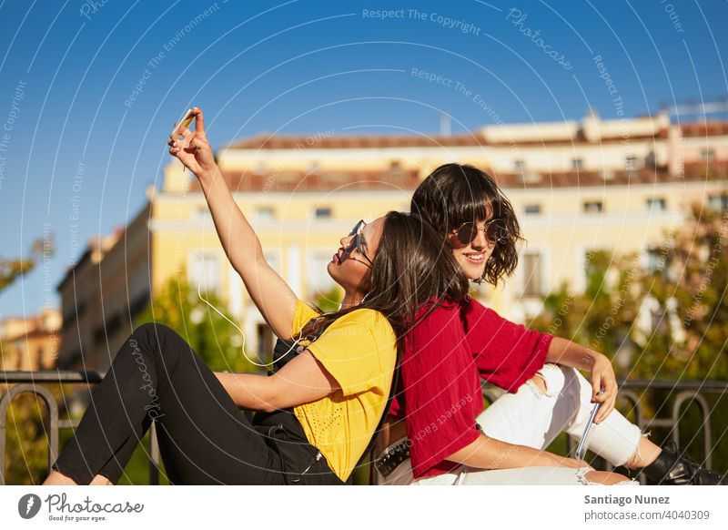 Two teenager girls sitting and taking selfie. madrid young people friendship lifestyle beautiful fun happy together leisure woman smiling teens cheerful female