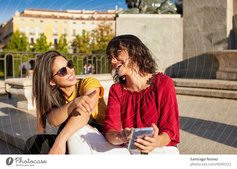 Two teenager girls sitting and laughing madrid young people friendship lifestyle beautiful fun happy together leisure woman smiling teens cheerful female youth