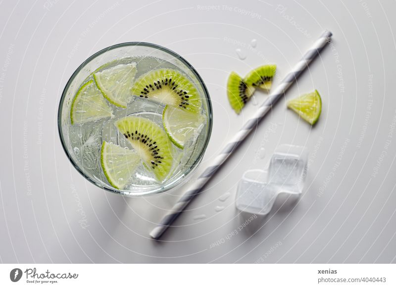 Flavored soft drink with kiwi, lime and ice cubes. Paper drinking straw is ready. Beverage Cold drink Kiwifruit Ice cube Refreshment Summer detox aromatic water