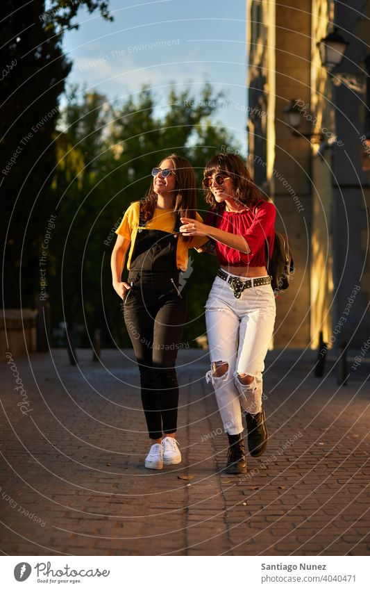 Two teenager girls walking down the street. madrid young people friendship lifestyle beautiful fun happy together leisure woman smiling teens cheerful female