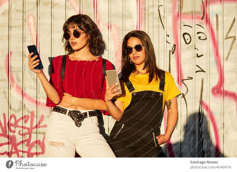 Two teenager girls standing and looking at their smartphone madrid young people friendship lifestyle beautiful fun happy together leisure woman smiling teens