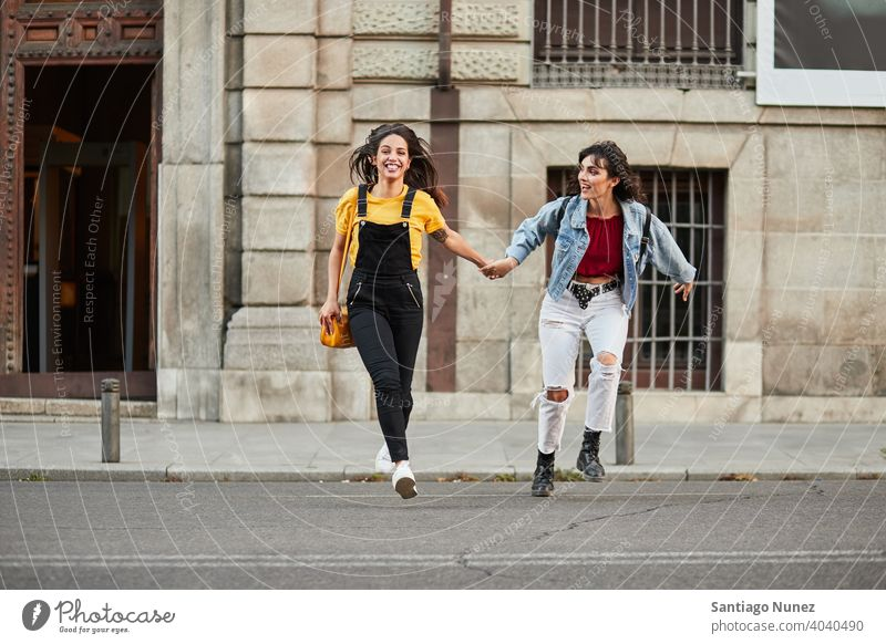Two teenager girls running down street. madrid young people friendship lifestyle beautiful fun happy together leisure woman smiling teens cheerful female youth