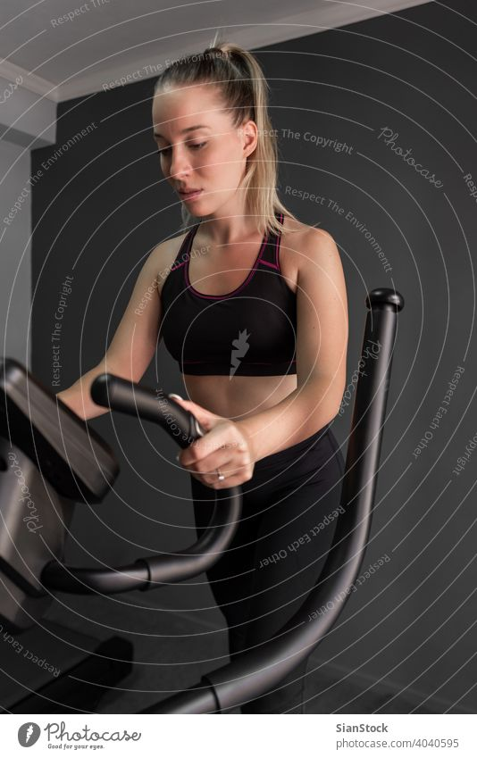 Woman Exercise Elliptical cardio running workout at fitness gym endurance people exercise training body elliptical trainer power treadmill athletic sport