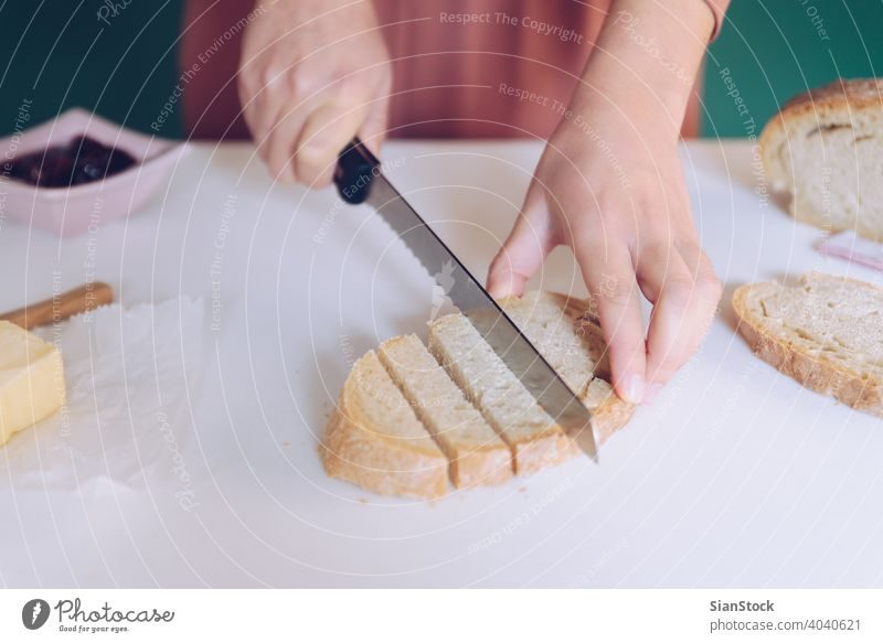 Woman cutting bread at  kitchen hands breakfast making green background dress marble cooking home toasted spoon table calories eating young protein jar