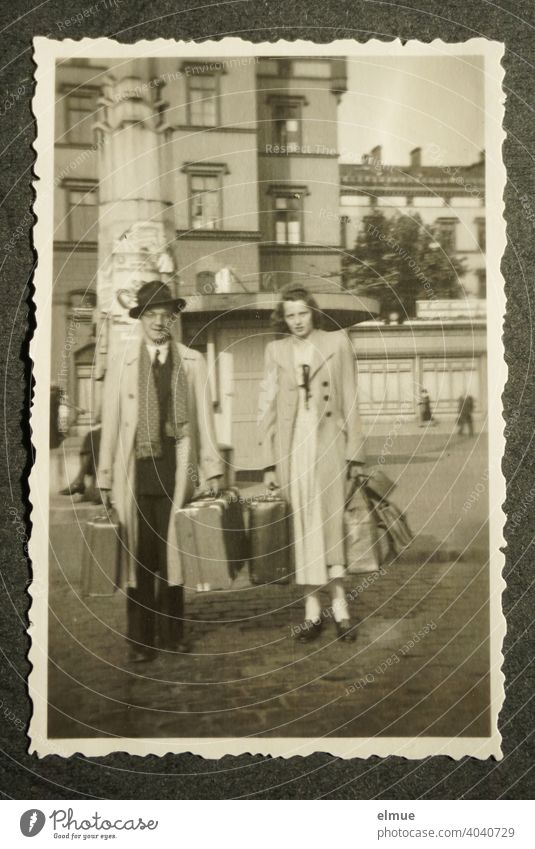 Black and white photo with deckle edge from the 1950s on a black photo album page, showing a young couple with travel suitcases / holiday trip / memories / analog photography