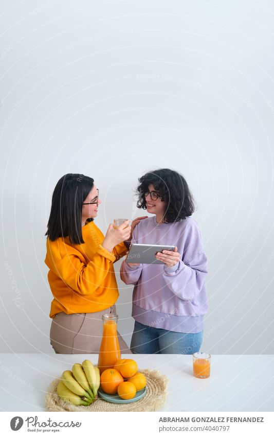 two young women using tablet. neutral background businesswoman caucasian communication cooperation digital tablet e-commerce eyeglasses friend friendship indoor