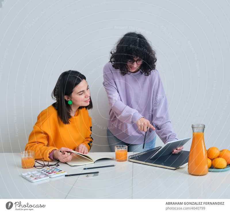 two young women in a creative studio using a tablet agency architect beautiful woman brainstorming caucasian cooperation creativity design digital tablet