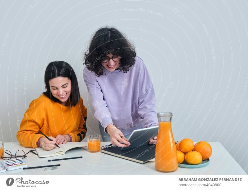 two young women in a creative studio using a tablet teamwork two people woman technology indoor digital tablet creativity design meeting drawing caucasian
