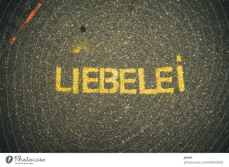 "A path with street painting or graffiti with the word ""LIEBELEI"" 