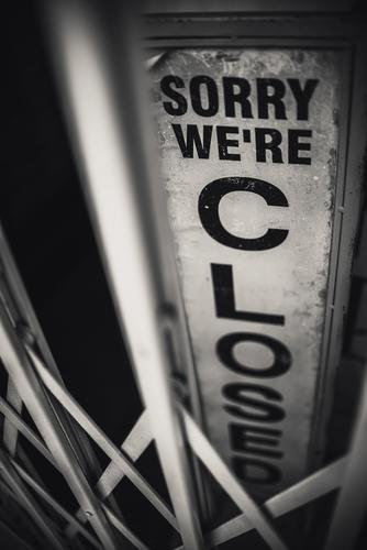 Still lockdown in retail, restaurants and hotels | A sign of a shop behind a locked bar door - black inscription on a light background: sorry we're closed I sorry, it's closed I corona thoughts