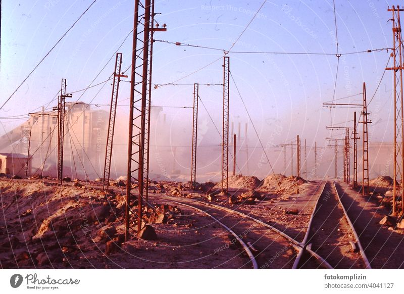 Railway tracks on factory site in the desert railway tracks rails Factory Factory site Industrial area Industry Electricity Transmission lines Cable Technology