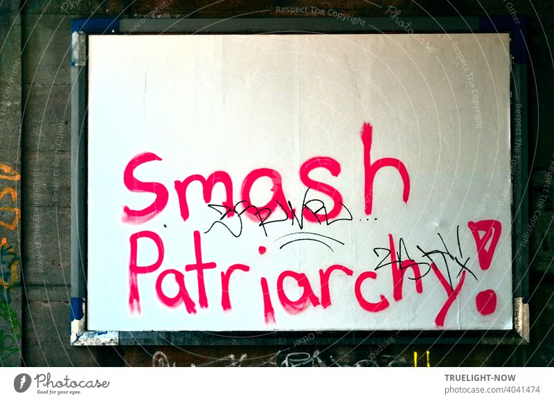Women's Day! Excited young women in wild rage used the will-less surrender of innocent white billboard wall for blood-red angry battle slogan. Smash Patriarchy!