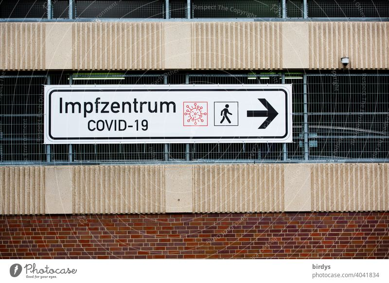 Signpost to the Covid-19 vaccination center. Vaccination center ,big sign at a parking garage vaccination centre covid-19 inoculate sb. pandemic Road marking