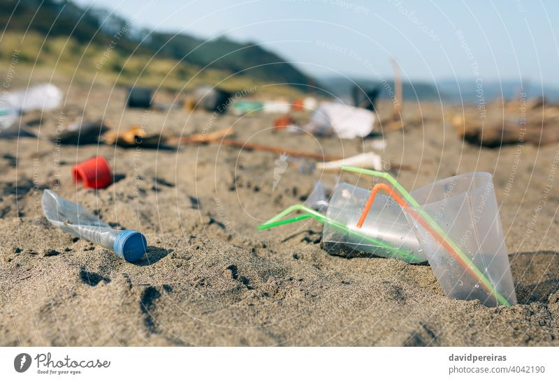 Dirty beach landscape full of waste trash garbage straws disposable cups plastic contaminated sand dirty environment nature pollution coast plastic lid rubbish