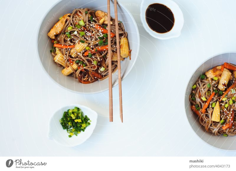 Japanese stir fried buckwheat soba noodles with chicken and vegetables - carrot, onion and baby corn served in bowl on white background food chopstick meal