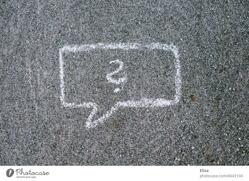 A speech bubble with question marks drawn on the road with chalk Speech bubble Question mark Perplexity asking Ignorance disorientation Chalk Insecure