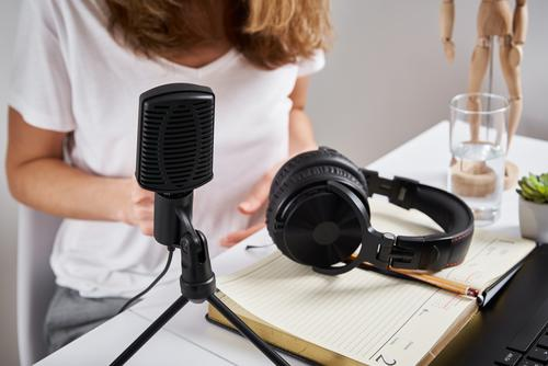 Podcast concept. Woman recording online course microphone headphones workplace podcast audio radio technology top view keyboard remote education learning