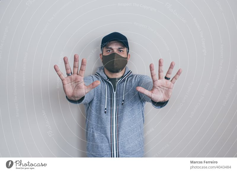man with mask stop hands face mask prevention caucasian warning safety young gesturing no people danger pandemic epidemic infection standing male flu