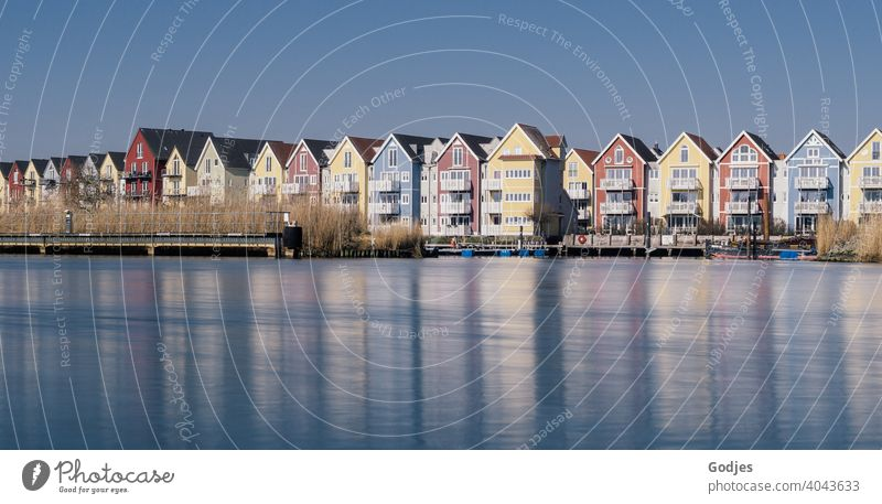 Long exposure of colorful wooden houses (swedish houses) with boat docks at a river Subdued colour Blue Lakeside Wide angle Copy Space bottom Cold