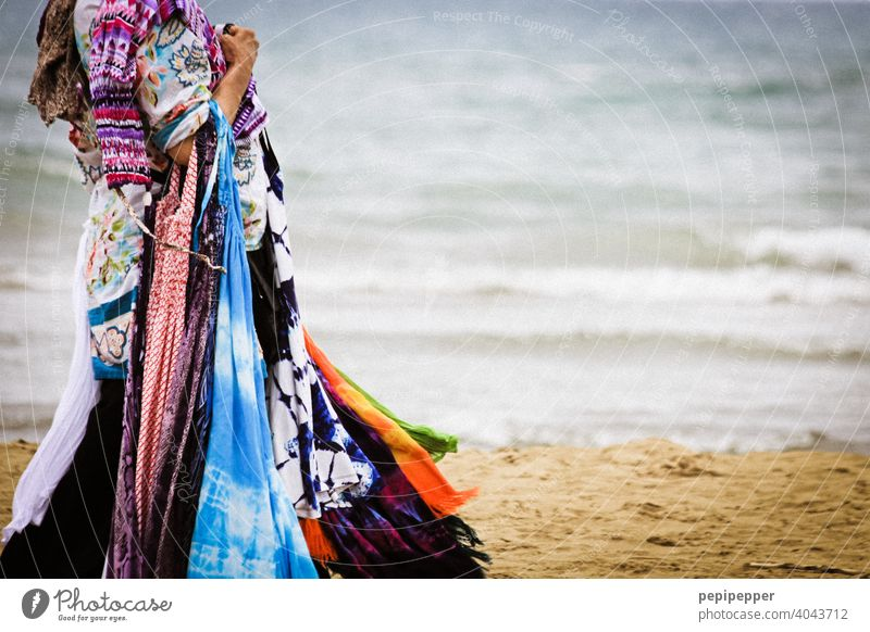 Woman selling scarves and summer dresses on the beach on vacation Beach Sell sale Shopping Trade Colour photo Business Fashion Commerce Customer consumer