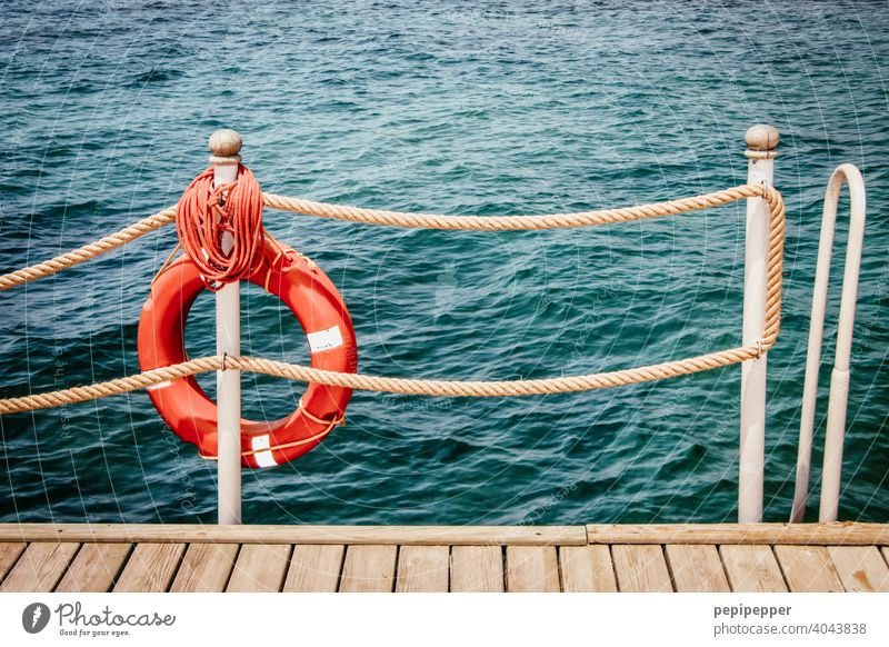 red lifebelt Life belt rescue tyre Lifebelts Navigation Colour photo Deserted Vacation & Travel Tourism Water Exterior shot Day Ocean wooden walkway Footbridge