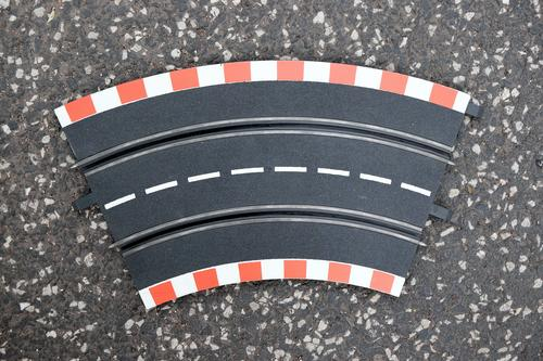 Curved part of a car racetrack with dotted white center line on grey asphalt at the flea market at the Golden Oldies in Wettenberg Krofdorf-Gleiberg near Gießen in Hesse, Germany