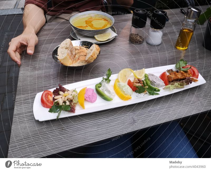Long narrow plate with colorful Turkish appetizers, bread basket and soup plate on the table in a restaurant in the North End of Frankfurt am Main in Hesse, Germany