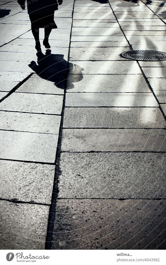 Running. Shadow Human being person Woman Senior citizen Going Light and shadow Boulevard walkway slabs Pedestrian precinct on one's own manhole cover