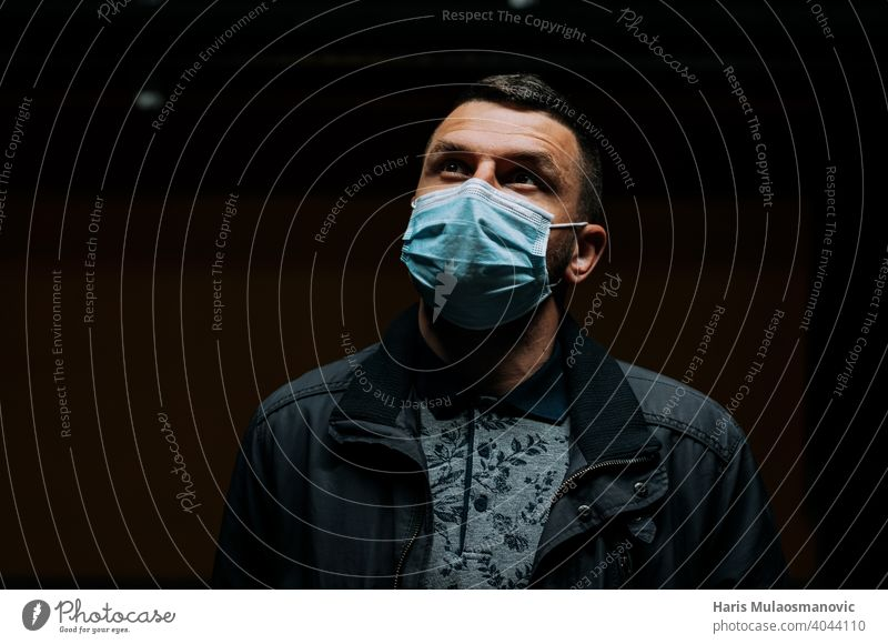 Portrait of man wearing a face mask and looking up on dark black background 19 adult apocalyptic breathe caucasian city concept coronavirus covid 19 covid-19