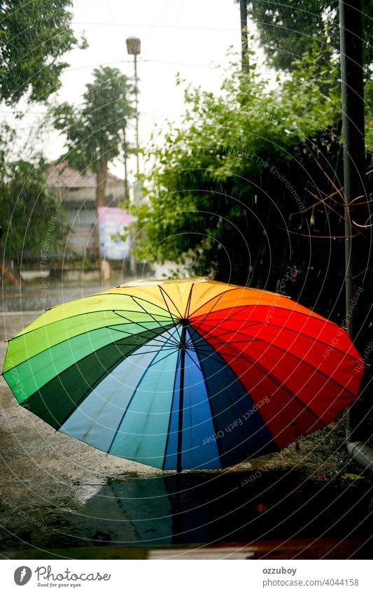 colorful umbrella on rainy day weather season wet outdoor water drop background nature protection raindrop fall storm outside spring safety blue climate red