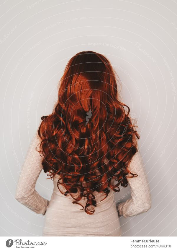 Back view of woman with long red curly hair in skin colored sweater Slim Red skin-coloured Curly Feminine Groomed Glittering Hair and hairstyles Woman
